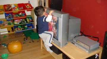 Toddler climbing on a tv