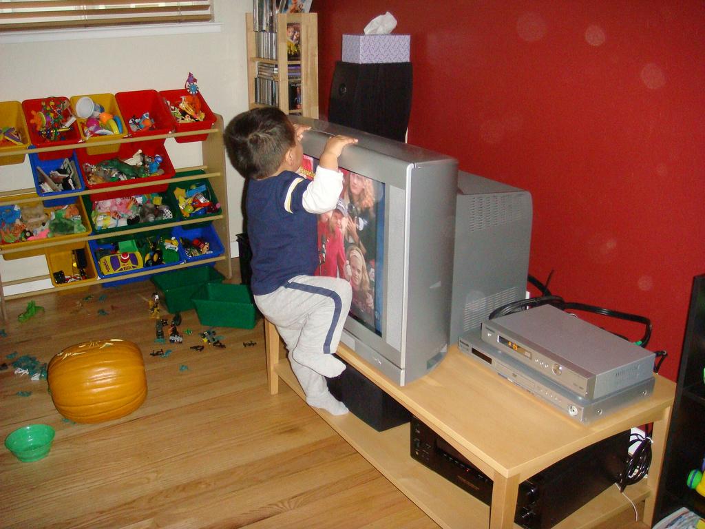 Toddler climbing on a tv