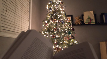 reading by the christmas trree